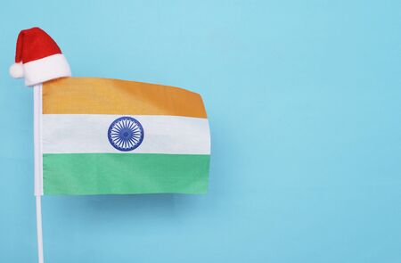 Flag of India with little santa claus hat on blue background. New Year winter holiday concept, copy space, beautiful 版權商用圖片