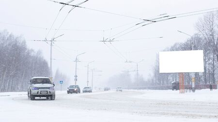 Road in the city with cars in the winter, a lot of snow. Billboard, place for text, copy space, outdoor 版權商用圖片