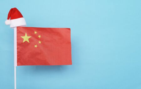 Flag of China with little santa claus hat on blue background. New Year winter holiday concept, copy space, beautiful