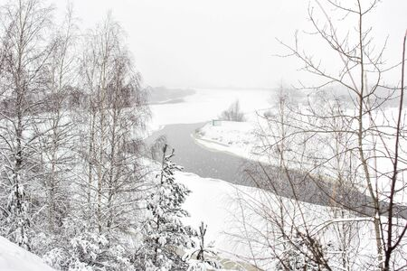 Winter river on a background of a snowy landscape, blizzard, background. Beautiful nature, climate 版權商用圖片