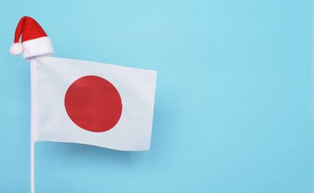 Flag of Japan with little santa claus hat on blue background. New Year winter holiday concept, copy space, beautiful