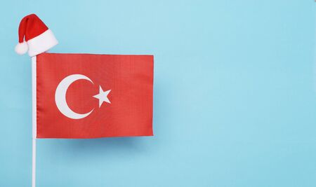 Flag of Turkey with little santa claus hat on blue background. New Year winter holiday concept, copy space, beautiful