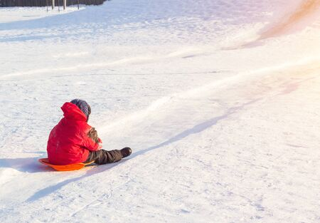 Little boy in bright red clothes rolls down a hill in frosty winter weather, copy space, outdoor Reklamní fotografie