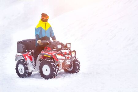 A man rides a lot of snow on an ATV in winter, background, quadracycle, copy space, transport