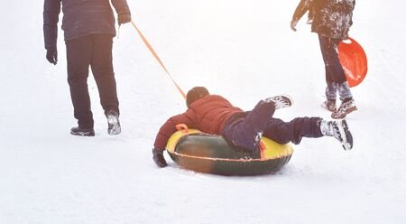 people climb a snowy mountain to move out of it. Winter roller coaster ride, background, morning 版權商用圖片