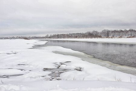 Winter nature, melted river through the snow. Cloudy winter day, background, copy space, outdoor