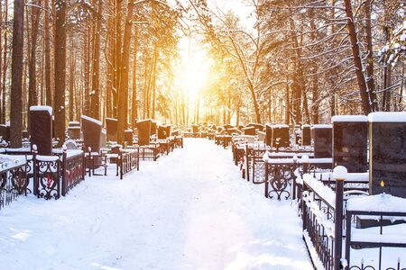 Winter cemetery in the background of the sun, alley. Copy space, graveyard