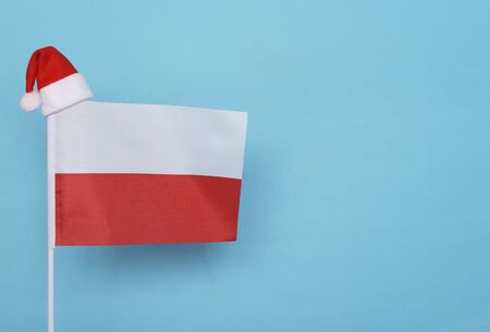 Flag of Poland with little santa claus hat on blue background. New Year winter holiday concept, copy space, beautiful