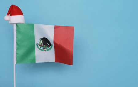 Flag of Mexico with little santa claus hat on blue background. New Year winter holiday concept, copy space, beautiful