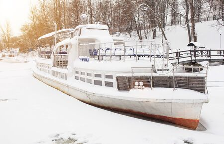 A ship swept by snow in the winter on a river, background Stock Photo