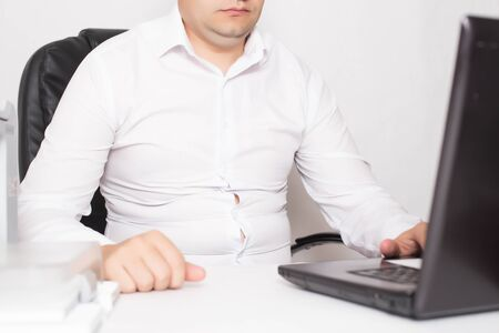 Male office worker with double chin and obesity at a laptop. The concept of malnutrition and sedentary lifestyles, adiposity