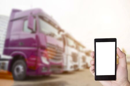 Hand with a phone on the background of parking with trucks. The concept of the application for truckers on the phone to search for goods, control the time of work and rest and find a parking spot, copy space, navigation Stock Photo