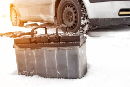Car battery against the background of a car in winter. Winter battery discharge concept, copy space, charging the battery
