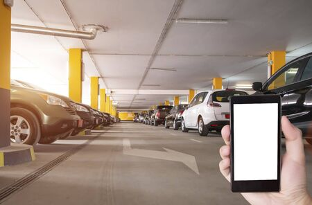 Hand with phone a white screen on the background of parked cars in the parking lot. The concept of applications for a smartphone to search for and protect a car in a parking lot, copy space, modern