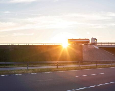 Truck driver on a large truck with a tanker carries cargo against the backdrop of a sunny sunset, copy space