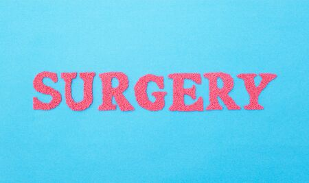 The word surgery made of red letters on a blue background. The concept of the section of medicine dealing with surgical operations in various fields of medicine