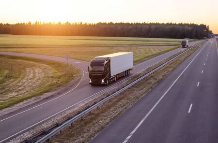 A caravan of modern freight trucks transports cargo in the evening against the sunset. Trucks drive on the motorway in the evening, logistic