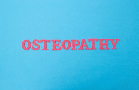 red osteopathy word on blue background. Alternative medicine section concept treating a person. Stockfoto