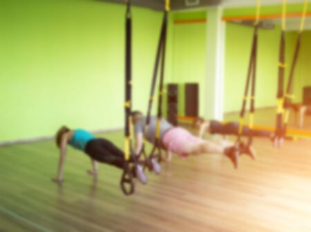 Group exercise in the hinged gym TRX where people do the push up hinge exercise, blurred, metabolic, gymnasium