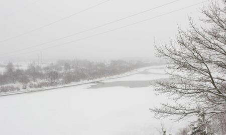 Winter river on a background of a snowy landscape, blizzard, background. Beautiful nature, climate Banque d'images - 135490619