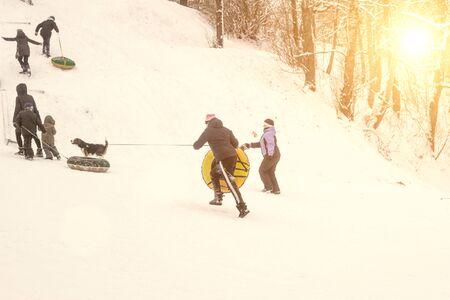 people climb a snowy mountain to move out of it. Winter roller coaster ride, background, morning Banque d'images - 135491325
