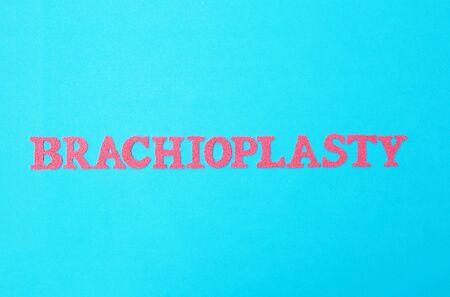 The word brachioplasty in red letters on a blue background. The concept of the modern procedure in plastic surgery for lifting the skin on the hands of a person, medical, cosmetology