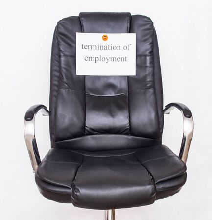 Black leather office chair on which the inscription termination of employment, The concept of layoffs and job cuts, workplace