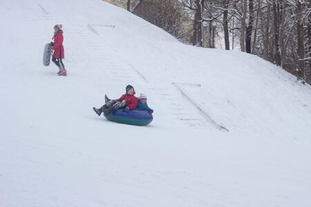 A lot of people children and adults ride a sled in the winter in the snow, gladness. BOBRUISK, BELARUS - 03.01.19 Sajtókép