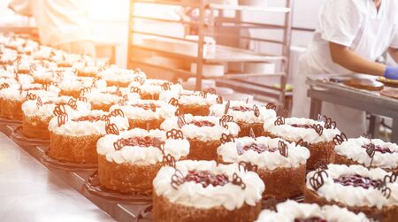 Making sponge cakes with cream at a confectionery factory. Cook decorates cake with cream, sweet dessert