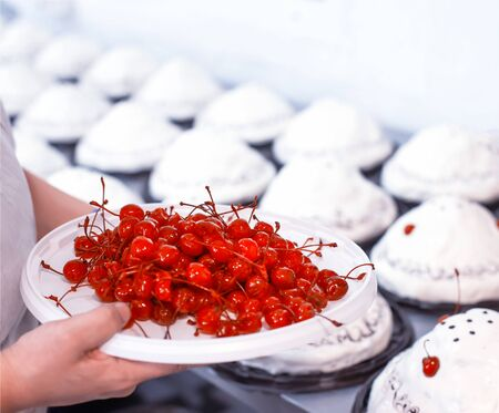 A chef decorates cakes in a confectionery factory with fresh cherry. Dessert mass production, background, industry
