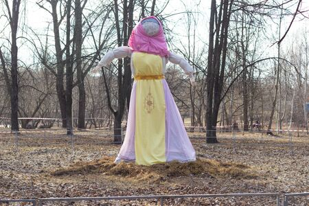 A scarecrow for inflammation by fire stands in nature. The traditional holiday of seeing off winter. Shrovetide