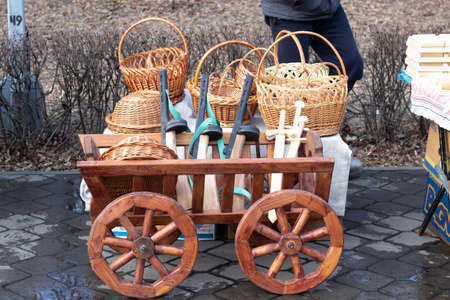 BOBRUISK, BELARUS 10.03.2019: Sale of wood products handmade. Wooden wagon with wicker baskets on it
