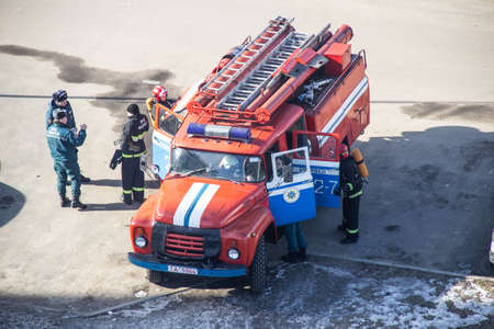 BOBRUISK, BELARUS 27.02.19: Firefighters climb out of a fire truck on an emergency call, evacuation