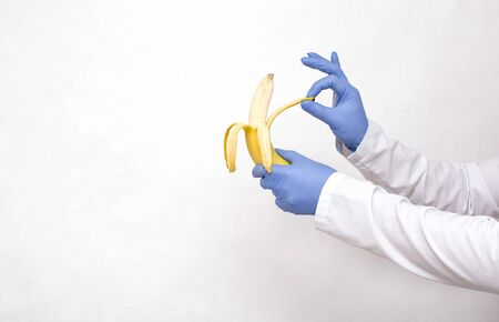 Dotkor holds a banana in his hands and peels. The concept of a surgical operation to dissect the frenum of the foreskin in men, circumcision of the foreskin, phimosis, copy space, healthcare