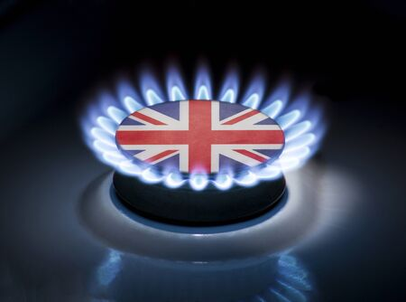 Burning gas burner of a home stove in the middle of which is the flag of the country of United Kingdom. Gas import and export delivery concept, price per cubic meter, transit, background, gasoline