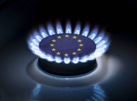 Burning gas burner of a home stove in the middle of which is the flag of the country of European Union. Gas import and export delivery concept, price per cubic meter, transit, background, gasoline