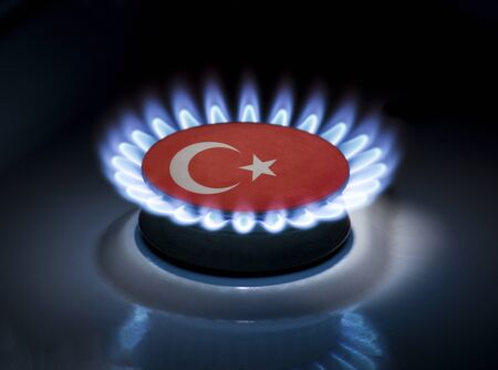 Burning gas burner of a home stove in the middle of which is the flag of the country of Turkey. Gas import and export delivery concept, price per cubic meter, transit, background, gasoline
