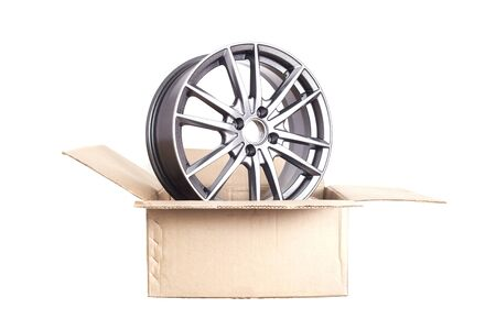 Cardboard box on a white background from which a car alloy disk sticks out in the form of rays, isolate
