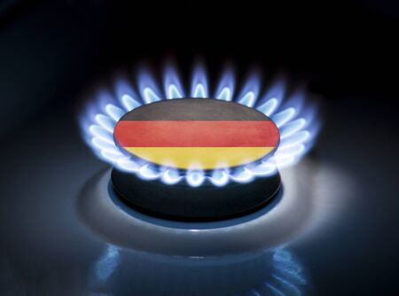 Burning gas burner of a home stove in the middle of which is the flag of the country of Germany. Gas import and export delivery concept, price per cubic meter, transit, background, gasoline Stock Photo