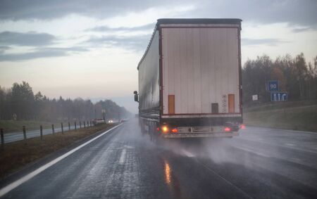 A truck with a trailer is being rebuilt on a motorway in a different row on slippery wet roads. The concept of security and attention to roads in bad weather, rain, accident