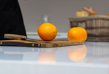 Juicy fresh oranges lie on a table in the kitchen and knife. The concept of proper nutrition and preparation of orange juice, copy space, background