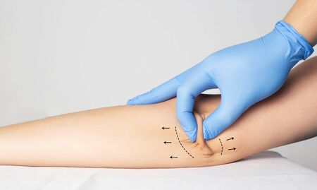 Doctor plastic surgeon examines the skin on the patients elbow. The concept of plastic surgery and skin tightening on the hands, copy space, healthcare