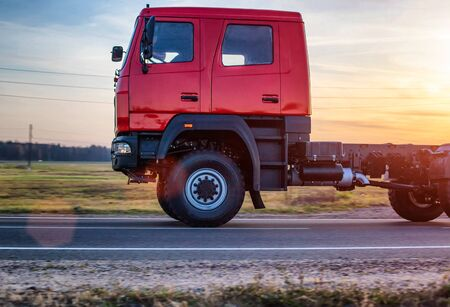 A new off-road truck rides on the road against a sunset. The concept of modern SUVs, departure for travel and expedition