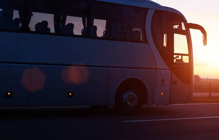 Modern comfortable passenger bus against the background of the orange sky with sunset rides on the highway. The concept of travel in Europe and passenger transportation in travel companies