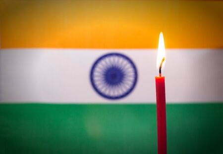 Burning candle on the background of the flag of India. The concept of mourning and sorrow in the country 스톡 콘텐츠