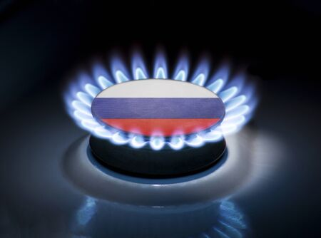 Burning gas burner of a home stove in the middle of which is the flag of the country of Russia. Gas import and export delivery concept, price per cubic meter, transit, background, gasoline