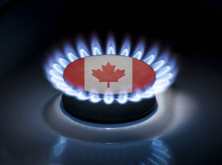 Burning gas burner of a home stove in the middle of which is the flag of the country of Canada. Gas import and export delivery concept, price per cubic meter, transit, background, gasoline