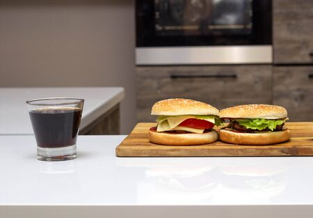 Two burgers and a glass of soda are in the kitchen. The concept of strong but tasty food