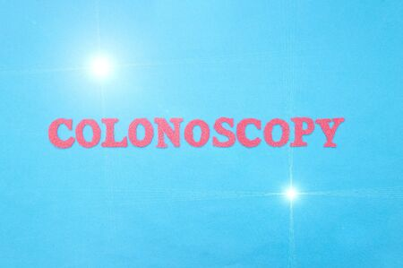 The word colonoscopy in red letters on a blue background. The concept of a medical diagnostic procedure for examining the colon and rectum in humans, intestinal cancer