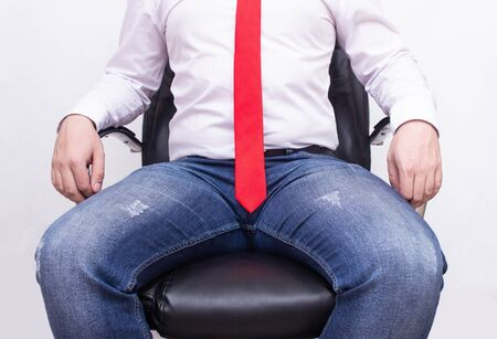 A male executive in an office is sitting in an office chair with a red tie spreading his legs. The concept of sexual harassment at work, cheating, romance at work, director 스톡 콘텐츠